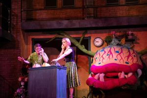 """Left to right: Logan Douglas, Sara Kuntz, and Glen Lee (inside the plant) performing during a dress rehearsal for """"Little Shop of Horrors."""""""