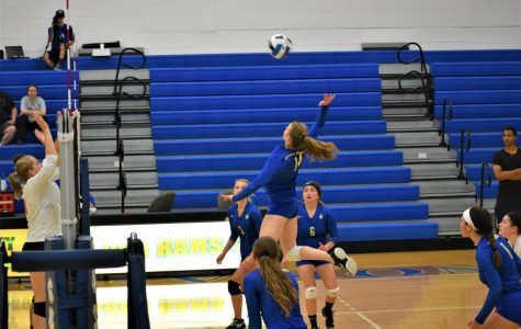Marcale Palm reaches up to spike the ball on Sept. 17 in the Anoka-Ramsey Performance Gym. New volleyball coach Brandon Bader watches.