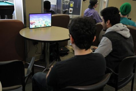"Two Anoka-Ramsey students playing ""Super Smash Bros. Ultimate"" in the Courtyard Commons."