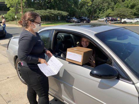Student receiving a box through their car window
