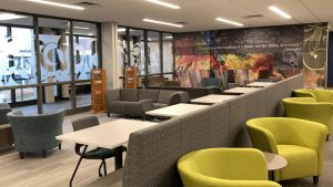 """ABOVE: A quote from Socrates, """"Education is the kindling of a flame, not the filling of a vessel,"""" can be seen through the new glass wall that lines the Library hallway."""
