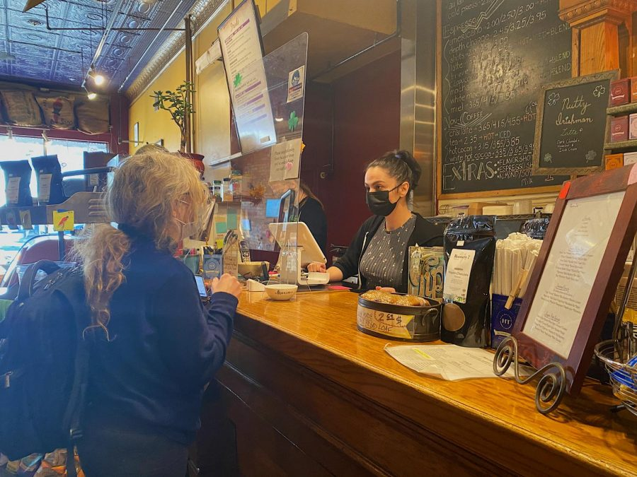 ABOVE: Avant Garden's barista, Cionah Salinas, taking a carry out order from customer Dana Pitzen while following COVID-19 prevention measures.
