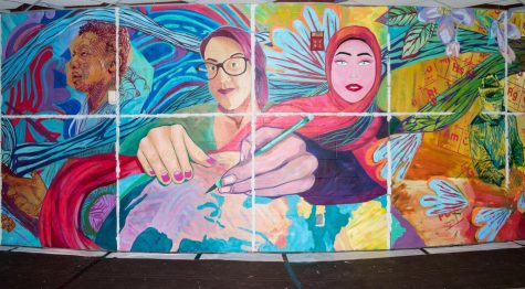 Sections of the mural of two women working together drawing a globe.