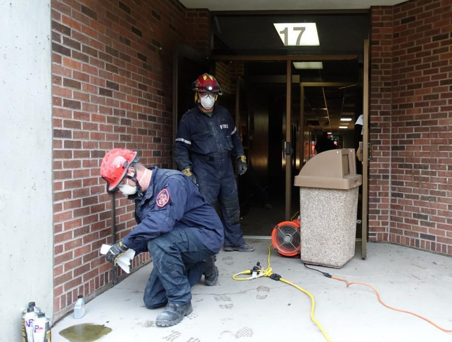 Masked firefighters prepare to entire the Business and Nursing building at the ARCC Coon Rapids Campus.