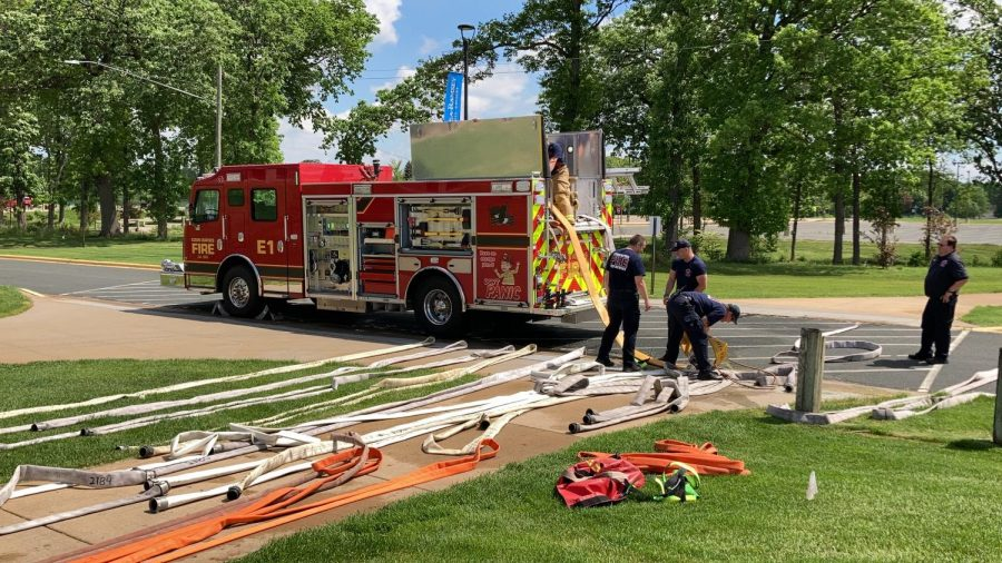 A group of firefighters work together to wrap up hundreds of feet of water hose on May 26.