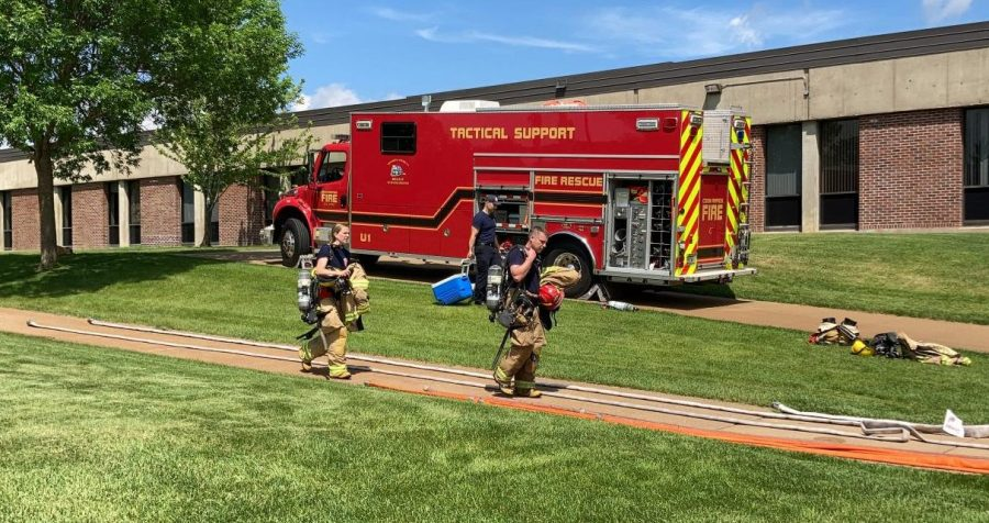 Two firefighters walk down the sidewalk on the south end of the Business and Nursing building on May 26.
